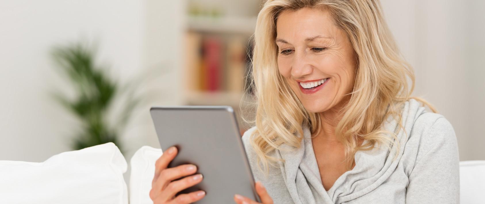 Frau schaut auf Tablet PC